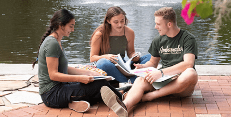 Students sit together by the water