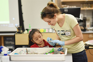 USFSM biology student Nicole Bill, right, assists a girl from UnidosNow.